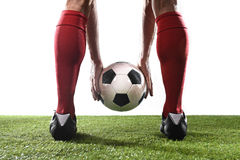 Nogi gracz futbolu trzyma piłkę w jego w czerwonych skarpetach i czerń butach wręczają umieszczać rzut wolnego Zdjęcie Stock