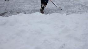 Nogi gracz w hokeja w łyżwach, kiju i krążku hokojowym na lodzie, ukazują się przy plenerowym łyżwiarskim lodowiskiem zbiory wideo