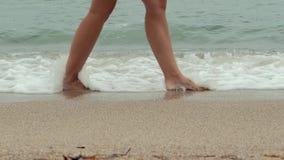 Nogi iść wzdłuż oceanu młoda kobieta wyrzucać na brzeg podczas wschodu słońca Dziewczyny kroczenie na mokrym piasku linia brzegow zbiory