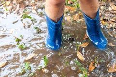 Nogi jest ubranym parę błękitni gumowi buty w wodnej kałuży dziecko zdjęcie royalty free