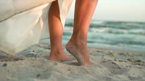 Nogi Kaukaska dziewczyna w bielu tęsk suknia na brzeg błękitny morze, stojaki na piasku, słońce, obiektyw wolny zbiory wideo