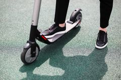 Nogi mężczyzna w eleganckim stroju stojaku na elektrycznej hulajnodze na ulicie zdjęcia stock
