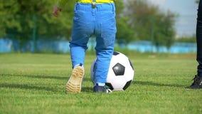 Nogi młoda kobieta bawić się z piłki nożnej piłką na zielonym gazonie stadium w wolnym zakończenie ruchu dziecko i _ zbiory