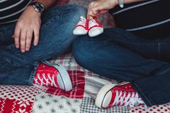 Nogi matka i tata ubierali w niebieskich dżinsach i czerwieni sneakers Matka trzyma dziecko czerwieni sneakers koncepcja w ciąży Fotografia Stock
