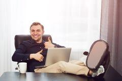 Nogi na biurku, laptopie i uśmiechniętym mężczyzna aprobat symbolu, Zdjęcia Royalty Free