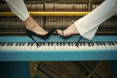 Nogi na fortepianowej klawiatury błękitnym kolorze, moda zdjęcia royalty free