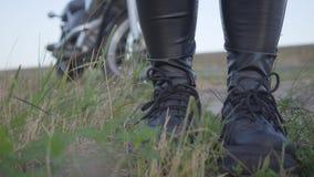 Nogi nierozpoznany rowerzysta stoi na trawie w polu w czarnych rzemiennych sneakers i spodniach Motocyklista dalej zbiory wideo