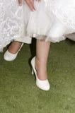 Nogi panna młoda w białych oblamowanie sukniach na zielonej trawie i butach Obraz Stock