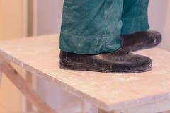 Nogi pracownik z zielonymi workwear i czerni butami na drewnianym stepladder Pracownik robi plasterboard drywall dla Zdjęcia Royalty Free