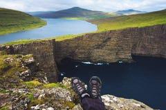 Nogi wycieczkowicza obsiadanie na górze falezy nad jeziornym Sorvagsvatn na Faroe wyspach fotografia stock