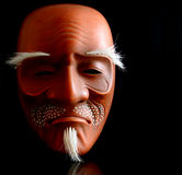 Noh Mask. Traditional Japanese Noh mask sidelit against black background royalty free stock photos