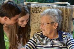 Noi e la nonna, fratelli germani sorprendiamo la loro grande-nonna fotografia stock libera da diritti
