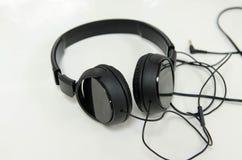 Noir d'écouteurs sur un fond blanc Photographie stock libre de droits