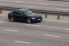 Noir de luxe BMW de voiture expédiant sur la route vide Image stock