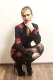 Noir de port de femme assez blonde et robe rouge se reposant sur la Floride images stock