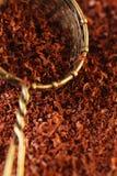 Noir du chocolat râpé par amende 100% dans le tamis Photo stock