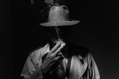 Noir Filmcharakter, der eine Zigarette raucht lizenzfreie stockfotografie