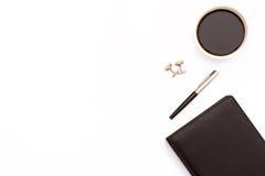 Noir, journal intime, stylo, boutons de manchette, et une tasse de café noir sur le fond blanc Photos libres de droits