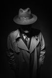 Noir movie character. Man posing in the dark with a fedora hat and a trench coat, 1950s noir film style character stock photo