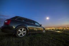 Noir parking la nuit dans les pr?s verts sur le fond de l'espace de copie des lumi?res des b?timents ?loign?s de ville et du ciel photo libre de droits