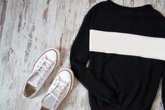 Noircissez avec le chandail blanc et les chaussures blanches sur un fond en bois Concept de mode Photo stock