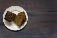 noircissez le pain coupé en tranches de ‹d'†de ‹d'†d'un plat blanc se tenant sur une table en bois Image stock