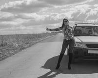Noire et blanche, la fille arrête la voiture, soulevant sa main sur un deser Images stock