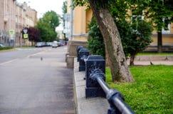 Noire, forgé, la balustrade en métal sur un bas mur de grès reculent dans la distance L'herbe et les arbres peuvent être vus par  Photo stock