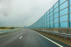 Noise-absorbing screens on the new road A-290 formerly M25 on the Taman Peninsula on a cloudy autumn day. The highway is part of the European route E97 stock photos