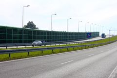 Noise barrier, acoustic screen, highway, cars on the sound-absorbing tunnel. Noise wall that protect residents against noise generated by cars stock image