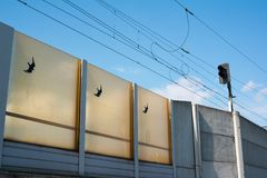 Noise barrier and soundwall. As protection against noise and acoustic pollution from noisy traffic of train and railroad transportation. Sound is reduced and Royalty Free Stock Photos