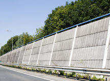 Noise control on higway. Long concrete wall next to highway to protect houses behind it from loud car sounds Stock Images