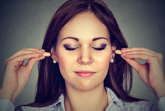 Noise control. Young woman with ear plugs. On gray wall background stock photo
