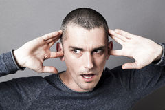 Noise and hearing concept for surprised man plugging ears Stock Photos