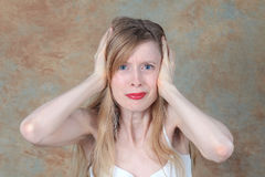Noise holding ears. Young woman holding her ears to protect them from loud noise stock photos