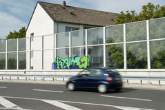 Noise Pollution. A noise protection wall between a busy road and a building royalty free stock photography