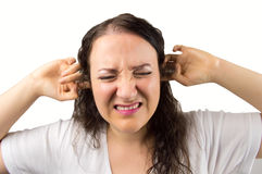 The noise upset the woman. Woman with hands in the ears disturbed with loud noise stock images