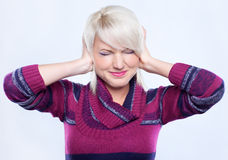 Noise. Young woman in woolen sweater protecting ears from noise stock photos