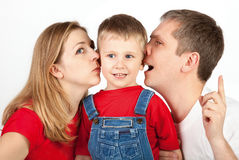 Noiseless Talking. Mother and father whisper in son's ears Royalty Free Stock Images