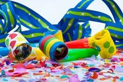 Noisemakers för ett parti på vitbakgrund med luftar banderoller och konfettiar Royaltyfri Fotografi
