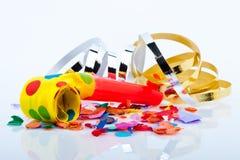 Noisemakers för ett parti på vitbakgrund med luftar banderoller och konfettiar Royaltyfria Bilder