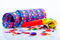 Noisemakers för ett parti på vitbakgrund med luftar banderoller och konfettiar Arkivfoton