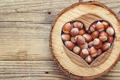 Noisette à un coeur en bois découpé sur le vieux fond en bois dessus Images stock
