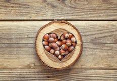 Noisette à un coeur en bois découpé sur le vieux fond en bois dessus Photographie stock
