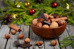 Noisettes et noix avec du chocolat et la cannelle dans une cuvette en bois Image stock