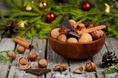 Noisettes et noix avec du chocolat et la cannelle dans une cuvette en bois Photos stock