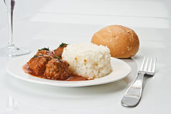 Noisettes with rice garnish. Noisettes with sauce and rice garnish on white dish Stock Images