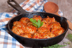 Noisettes are stewed in the tomato sauce in a frying pan. On the desk Royalty Free Stock Images