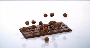 Noisettes tombant sur le comprimé de chocolat au lait clips vidéos