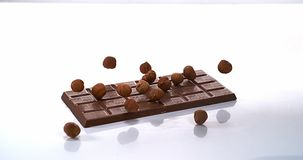 Noisettes tombant sur le comprimé de chocolat au lait banque de vidéos